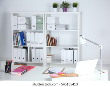 Modern office interior with tables, chairs and bookcases