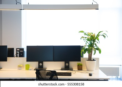 Modern office interior with two black monitors on beige desk and hanging lamps on top