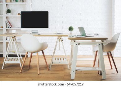 Modern office interior with white wooden furniture, empty computer and laptop on desk and other items. Mock up