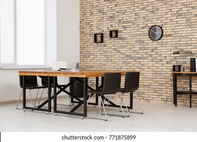 Modern office interior with wooden tables and chairs