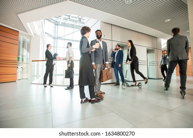 Modern office lifestyle: business people talking and walking while their colleagues riding scooters over spacious corridor