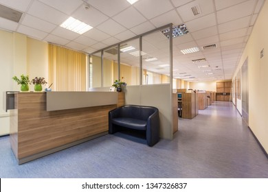 Modern office with open space and large windows. Reception desk