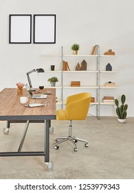 Modern office room, decorative wooden table yellow chair and bookshelf background, white wall with frame.