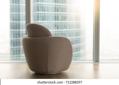 Modern office room with empty designer chair near full length big panoramic glass window and urban city skyscraper outside, luxury contemporary apartment interior, furniture for relaxation, rear view