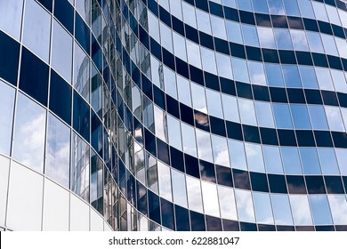 modern office skyscraper with glass windows and blue sky reflection