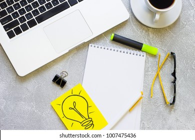 Modern office table desk, flat lay, top view. Workplace with a laptop, glasses, coffee cup,yellow light bulb image and a blank notepad , grey concrete background