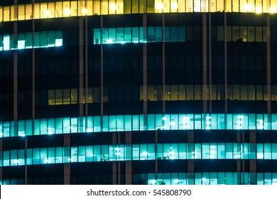 Modern office windows of skyscraper glowing at night