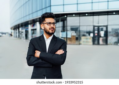 A modern office worker, an Indian man, a bank employee in a black suit, behind a large wooden building.