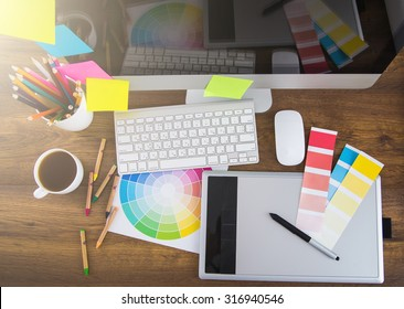 Modern office workplace with digital tablet, notepad, colorful pencils, glasses, in morning