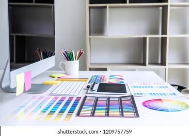 Modern office workplace with tablet, Graphic designer and color swatch samples at workplace.