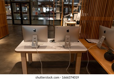 Modern office workspace station with apple iMac computers on a wooden white table - Creative space and work - Abu Dhabi, UAE, December 16, 2019