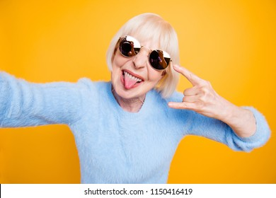 Modern old lady take selfie picture showing sign rock and roll isolated on bride yellow background