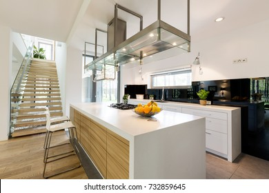Modern open plan kitchen area with wooden and metal detail in decoration