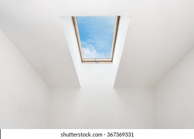 A modern open skylight (mansard window) in an attic room against blue sky