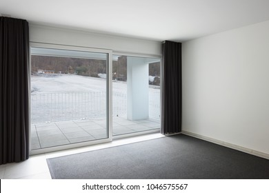 Modern open space with living room and kitchen. Large windows with a view. Nobody inside