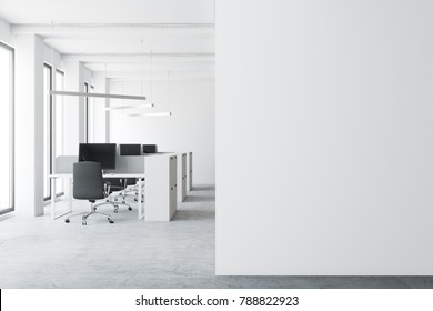 Modern open space office environment with a concrete floor, tall windows, and cubicles with computer tables. A white wall fragment. 3d rendering mock up