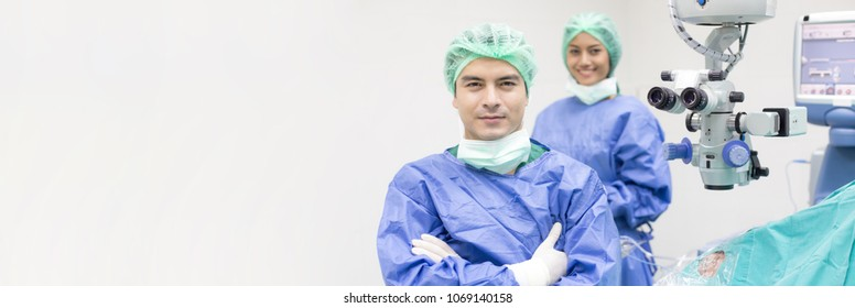 In a Modern Operating room Doctor and team looking to camera with smile. Banner size.