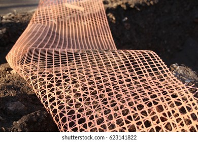 Modern orange safety fence (polymeric mesh grid) closeup