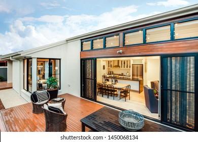 Moderner Außenbereich mit Holztäfelungen und Doppeltüren, moderner Küche und natürlichen Farbtönen