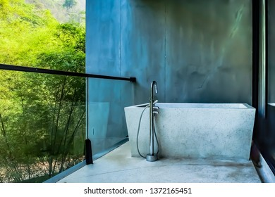 Modern outdoor bathtub on the terrace with and gerden view background