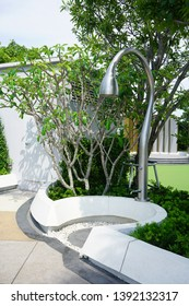 Modern outdoor shower area surrounded by planting within swimming pool area. Landscape detail design.