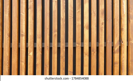 Modern outside wall covering with vertical wooden slats for texture or background. Contemporary slatted screen ideal for use as partitioning or fence. Smooth-planed and rounded slats of panel shield.
