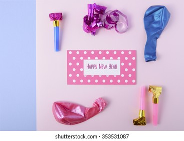 Modern overhead Happy New Year party decorations in pink and blue theme with greeting text.