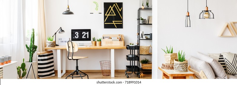 Modern painting on white wall above desk with desktop computer in multifunctional home office with copper basket