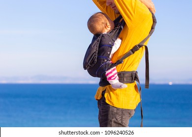 Modern parenting. Dad with baby daughter in  a carrier in the beach