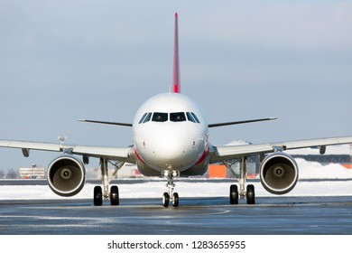 Modern passenger aircraft on the airport runway. Airplane front view. Winter time.