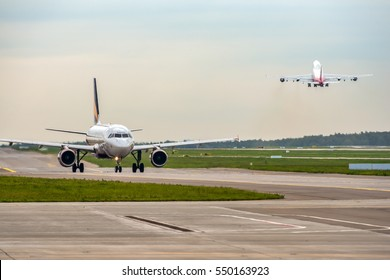 Modern passenger airplane taxiing while big widebody aircraft taking off at airport.