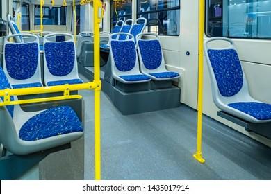 Modern passenger bus salon. City bas interior. Passengers seats. Handrails for holding. Contactless payment transport validators. Comfortable passenger urban transport. Public land transport.