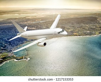modern passenger business jet airplane flying at sunset over scenic ocean coast with beautiful sun reflections water background aerial panoramic air travel transportation landscape golden light scene