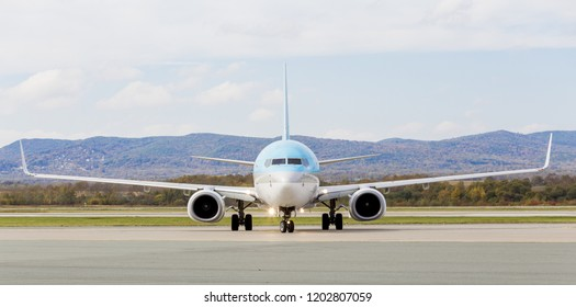 Modern passenger jet aircraft on runway. Nice fall on background. Journey and holidays concept.