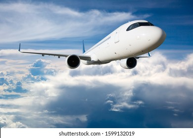 Modern passenger plane in flight. Aircraft flies high in the sky over the clouds. Aircraft front view. Close up.