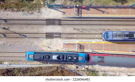Modern passenger train leaving a train station - Aerial image