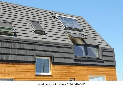 Modern passive house roof with attic skylight windows, solar water heater, solar panels, asphalt shingles.