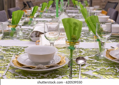 """Modern Passover Seder table with green  and gold decorations in Tel Aviv, Israel, complete with Matzos and a traditional Seder Plate.  Matzo cover reads """"Afikoman"""" in Hebrew."""