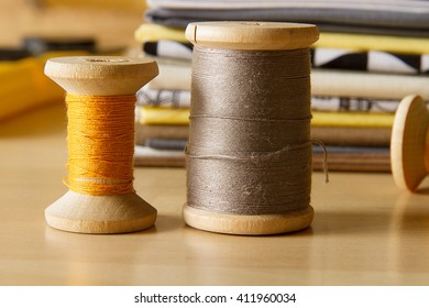 Modern patchwork fabrics in black, brown, white, yellow and grey on the wood table with yellow and grey sewing spools
