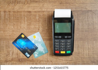 Modern payment terminal and credit cards on wooden background, top view. Space for text