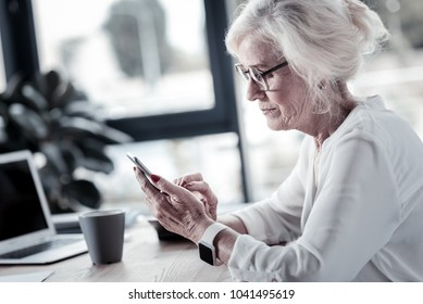 Modern pensioner. Attentive female person sitting in semi position and looking at her telephone while typing message