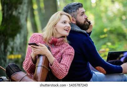 Modern people always involved online communication. Internet addiction. Online life modern technology. Logout of all accounts. Modern life. Happy loving couple relaxing in park with mobile gadgets.