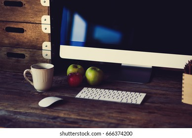 Modern personal computer with large monitor standing on natural materials. Cozy workspace with keyboard, mouse and ripe apples for lunch.