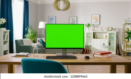 Modern Personal Computer with Mock-up Green Screen Display Standing on the Desk of the Cozy Home Office. Living Room of Stylish Interior Designer.