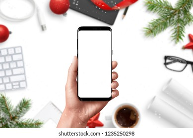 Modern phone mockup. Hand holding smart phone. Christmas decorations in background on office desk.