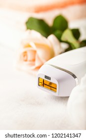 Modern photoepilator with bath accessories on light background.