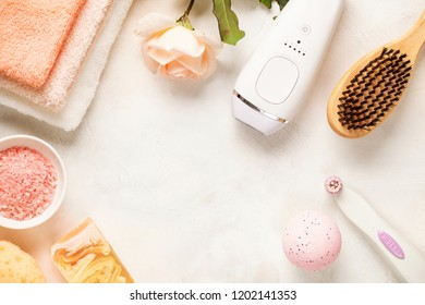 Modern photoepilator with bath accessories on light background. Top view