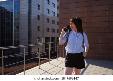 modern photographer happy girl in a leather cut for the camera against the backdrop of skyscrapers. woman wearing a blue shirt, black shorts and white trendy sneakers space for text