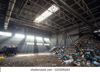 Modern plant for processing and sorting of municipal urban waste - evening sunlight in huge reception junkyard room, hangar for unloading waste from trucks and further processing sorting and reuse.
