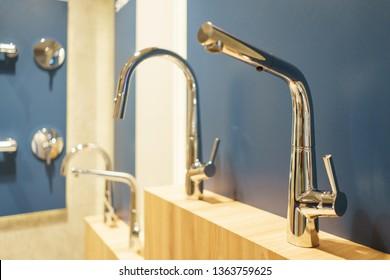 Modern plumbing for a stylish luxury bathroom. Several metallic shiny steel taps on a wooden blue wall. Bathroom equipment. Plumbing.